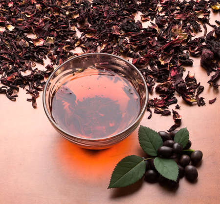 black red: Still life cup of black tea with mint leaves on dried karkade tea background