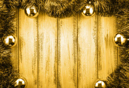 christmas backdrop: New year theme christmas tree decoration and gold balls on retro stylized wood background golden filtered