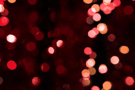 blured: Abstract blured background of dark red shiny Christmas tree decorations at night