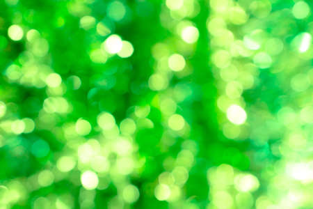 de focus: Abstract blured background of green shiny Christmas tree decorations