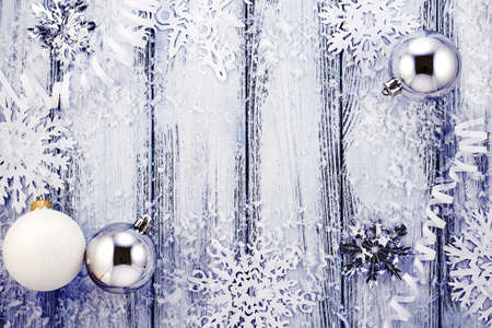 New year theme: Christmas tree white and silver decorations, balls, snow, snowflakes, serpentine on white retro stylized wood background with violet backlight Standard-Bild