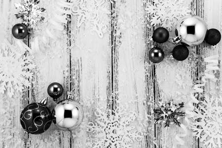 christmas backdrop: New year theme: Christmas tree white and silver decorations, balls, snow, snowflakes, serpentine on white retro stylized wood background black and white