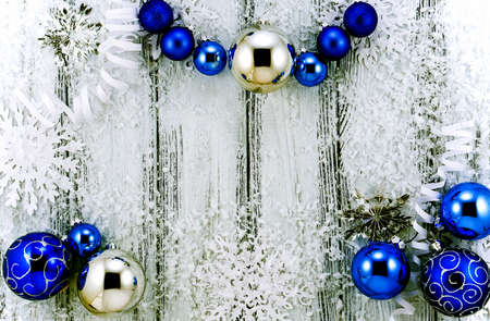 contrasted: New year theme: Christmas tree white and silver decorations, blue balls, snow, snowflakes, serpentine on white retro stylized wood background contrasted Stock Photo