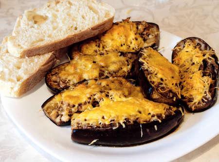 queso rallado: Barcos de calabacín rellenas de carne, arroz, tomate, champiñones y queso rallado con pan en la placa blanca contrastaba foto