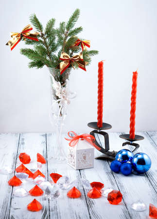 diamond candle: Christmas tree in white decorative goblet, white gift box, blue balls, candlestick with red candles and decorative stones on retro vintage white table on white background Stock Photo