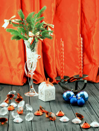 diamond candle: Christmas tree in white decorative goblet, white gift box, blue balls, candlestick with red candles and decorative stones on retro vintage brown table on orange cloth background