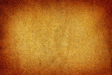 vignetting: Brown and yellow fabric woven texture macro background high contrasted with vignetting effect