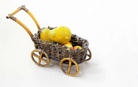shopping carriage: Wicker decorative cart with fruits on white background Stock Photo