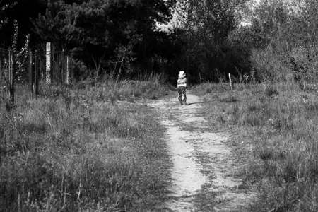 threshold: Little girl on the threshold of a dark forest black and white Stock Photo