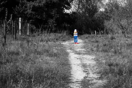 astray: Colored little girl on the threshold of a dark forest black and white