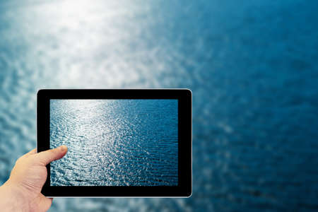 deflection: Tablet photography concept. Taking pictures on a tablet. Blue water with sun reflections