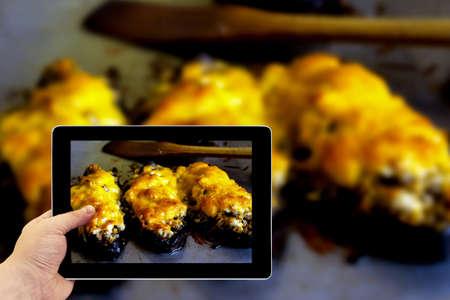queso rallado: Tablet photography Concepto. Tomar fotos en una tableta. Barcos de calabacín berenjena rellenos de carne, arroz, tomate y champiñones con queso rallado en la bandeja de horno