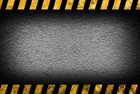 hazard stripes: Grunge grey wall background with black and yellow warning stripes Stock Photo