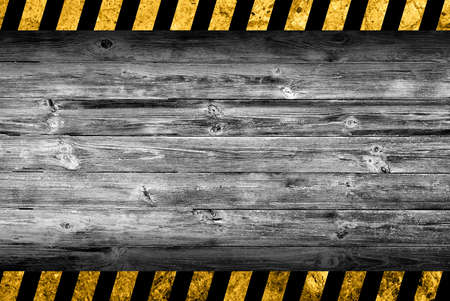 Grunge grey wood background with black and yellow warning stripes Imagens