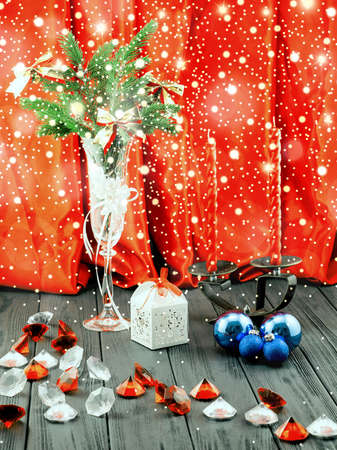 Christmas tree in white decorative goblet, white gift box, blue balls, candlestick with red candles and decorative stones on retro vintage brown table on orange cloth background with shiny snowfall Stock Photo