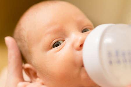Cute newborn baby drinking milk from a bottle. Stock photo Stock Photo