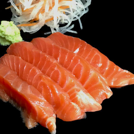 Sashimi Sushi set with salmon, tuna, wasabi and shredded radish are on the black background. Selective focus. Isolated picture.