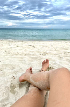 The girl who has sandy legs is laying down on the beach. Sandy beach tourist who wearing Anklet bracelet on her left ankle is crossing her legs on the beach. Stock Photo