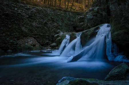 Frozen waterfall under old stone bridge