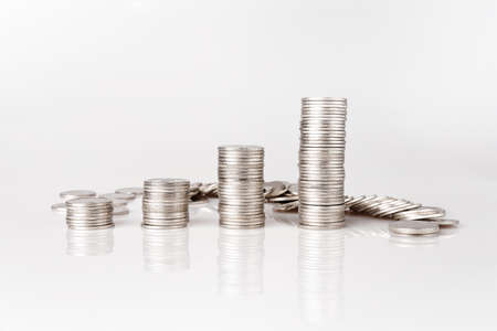 Silver coins piled on the white background Money saving ideas Banco de Imagens