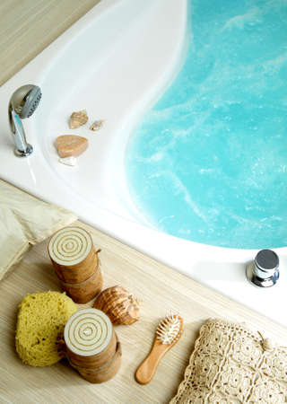 salt water: Bath tub filled with water, with candles, sponge and soap Stock Photo