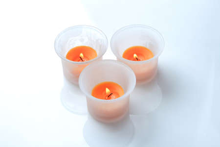 Three orange candles in a glass holder, on a white background photo