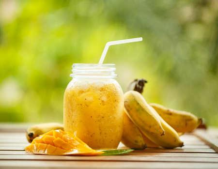 licuado de platano: Batidos de mango y plátano en un frasco de vidrio