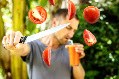 juice fresh vegetables: Man drinks tomato juice and cuts tomatoes simultaneously. Stock Photo