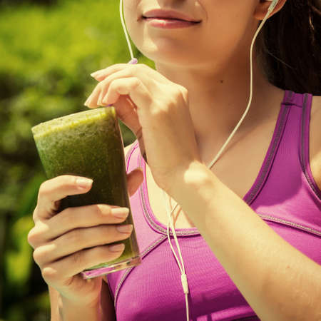 athletic girl: Athletic girl holding a green smoothie Stock Photo