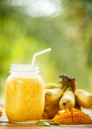 mango fruta: Smoothies mango and banana in a glass jar