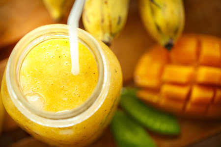 fruit juices: Smoothies mango and banana in a glass jar