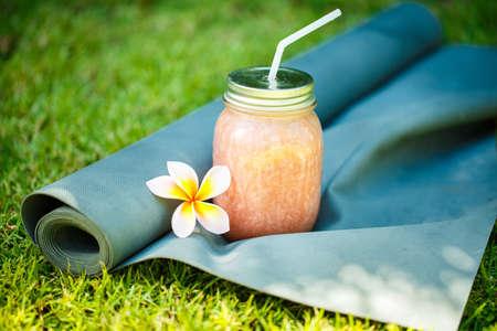 Smoothies und Yoga-Matte auf dem Rasen Standard-Bild