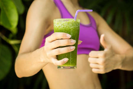 diet concept: Athletic girl holding a green smoothie Stock Photo