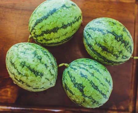 Small watermelon on wooden board