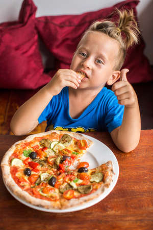 4 year old: 4 year old boy eating pizza in a restaurant