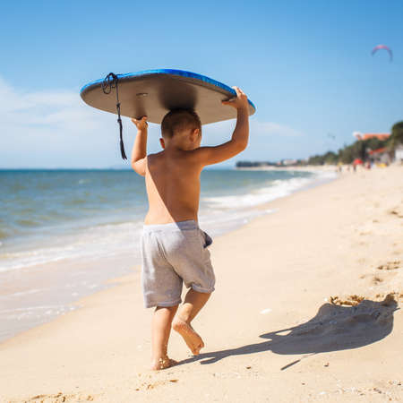 4 year old: 4 year old boy with a surfboard Stock Photo