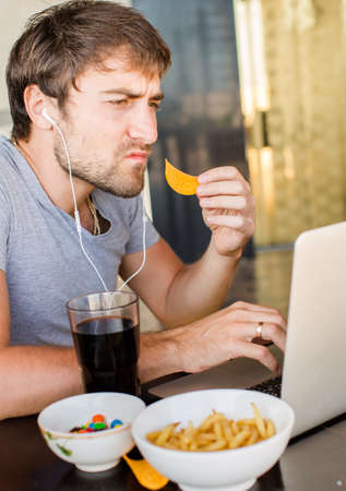 unhealthy lifestyle: Man working at the computer and eating fast food. Unhealthy Lifestyle.