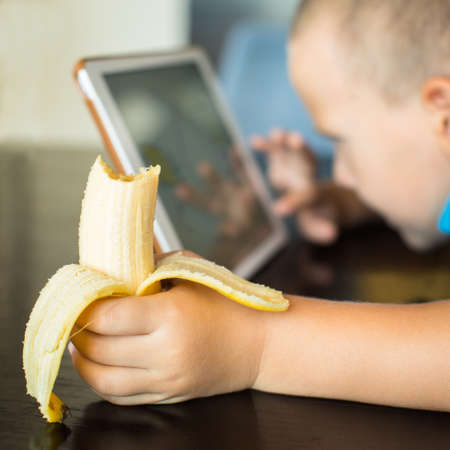 games hand: Adorable boy, eating his banana, while watching movie on tablet