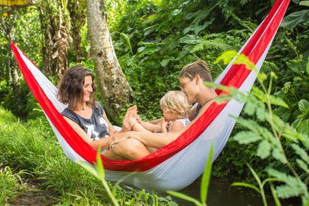 happy family nature: Happy young family spending time together in a hammock in green nature.