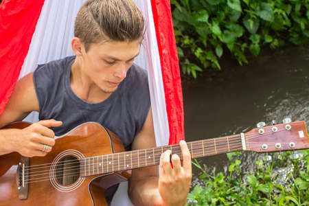 composing: Young man composing music with a guitar in a hammock in the forest. Stock Photo