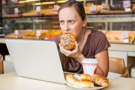 negocios comida: Bastante joven mujer que trabaja en la computadora y comer pan. Estilo de vida poco saludable