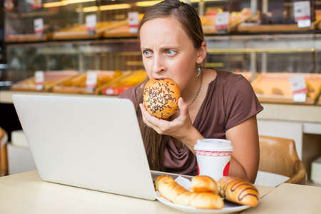 Pretty young woman working at the computer and eat bread. Unhealthy Lifestyle Stockfoto