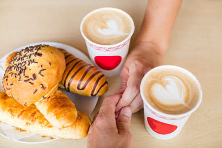 cup four: Four hands wrapped around a cup of coffee with heart drawing