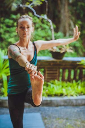 janu: Female meditating in tropical rainforest.