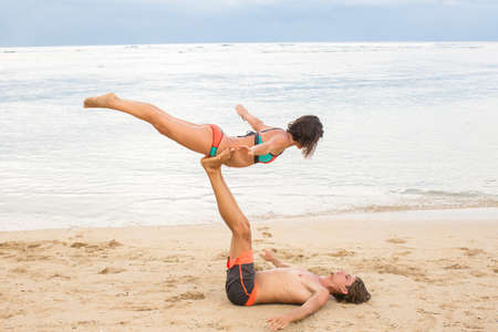 instance: Young couple  practice an exercise in trust on a tropical beach