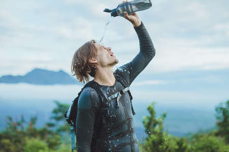 alpine water: Outdoor portrait of Young man looking on Batur volcano and Agung mountain view at morning from Kintamani, Bali, Indonesia and drink water