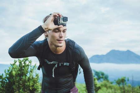 Aantrekkelijke Traveler vith camera op zijn hand tegen de Batur vulkaan van Kintamani, Bali, Indonesië