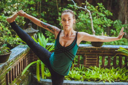 janu: Yoga woman doing Meditation and balance exercise in the tropical garden