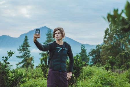 snapshot: Tourist takes a snapshot of the Batur volcano from Kintamani, Bali, Indonesia