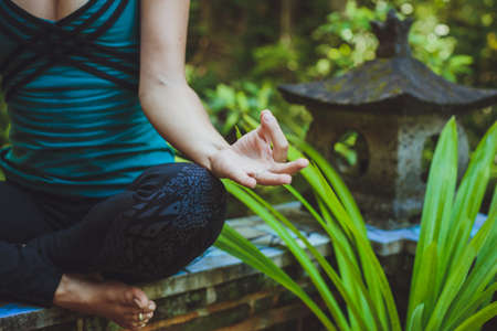 woman pose: A Young woman doing meditation outdoors in tranquil environment Stock Photo